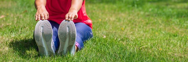 Kvinna som gör sträcka övningar, medan sitta på naturligt grönt gräs som är utomhus- på trädgården, utomhus- genomkörarebegrepp f royaltyfri bild