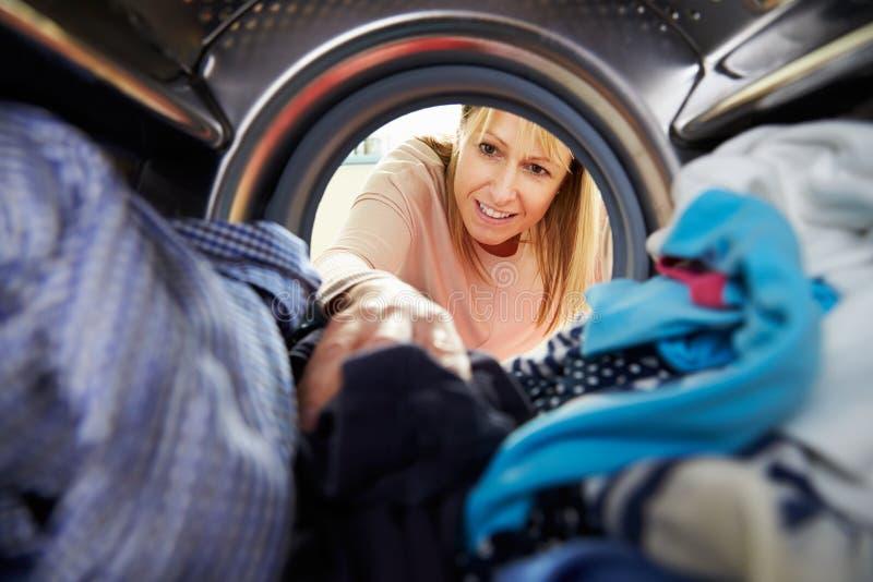 Kvinna som gör tvätterit som når den inre tvagningmaskinen arkivbild