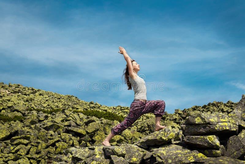 Kvinna som gör yogaövning på ny luft med blå himmel på backgrou royaltyfri foto