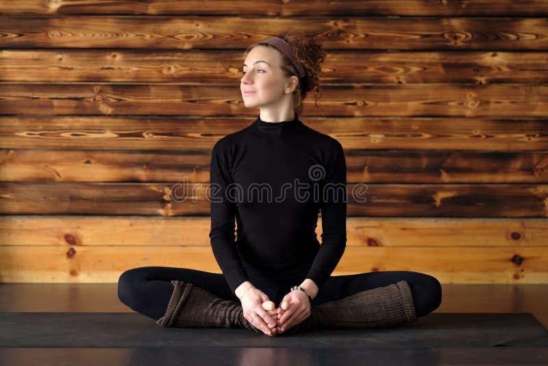 Kvinna som gör yoga- eller pilatesövningen som sitter i baddhakonasana fotografering för bildbyråer
