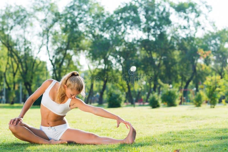 Kvinna som gör yoga i parkera royaltyfri bild