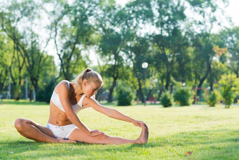 Kvinna som gör yoga i parkera arkivbilder