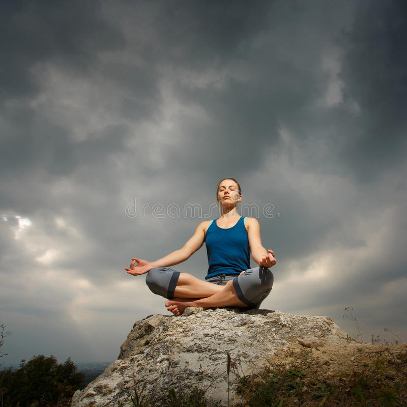 Kvinna som gör yoga mot inställningssolen royaltyfri foto