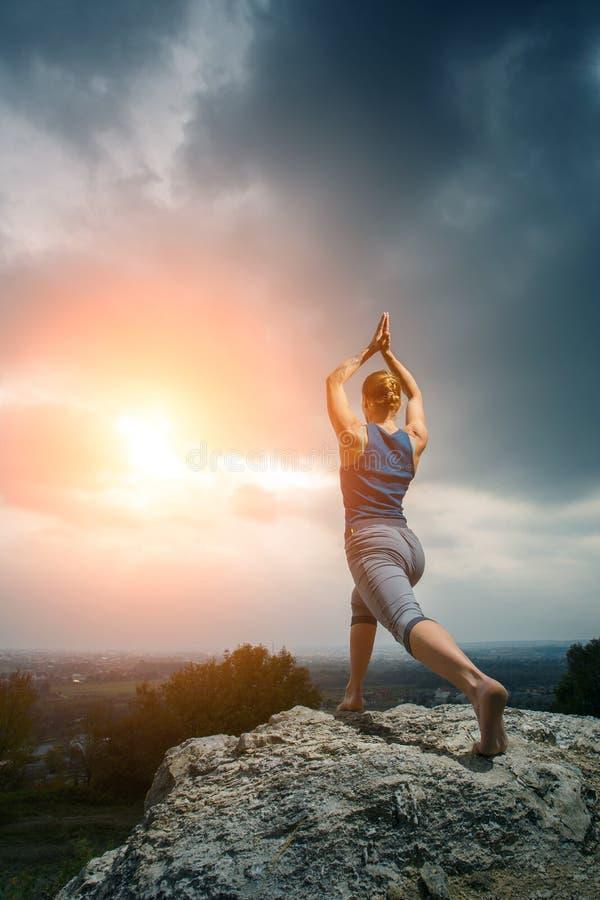 Kvinna som gör yoga mot inställningssolen royaltyfria bilder