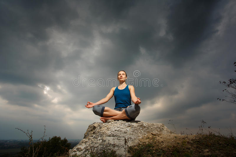 Kvinna som gör yoga mot inställningssolen fotografering för bildbyråer