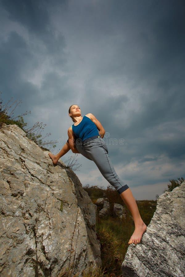 Kvinna som gör yoga mot inställningssolen arkivfoton