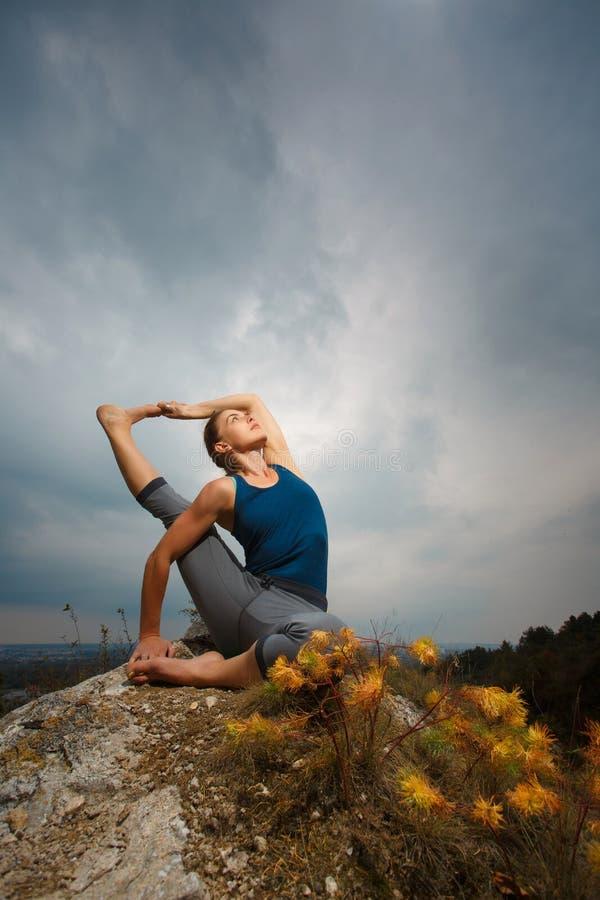 Kvinna som gör yoga mot inställningssolen royaltyfri fotografi