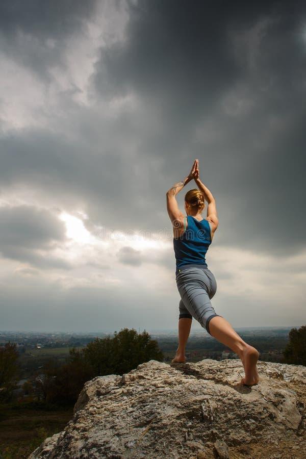 Kvinna som gör yoga mot inställningssolen royaltyfria foton