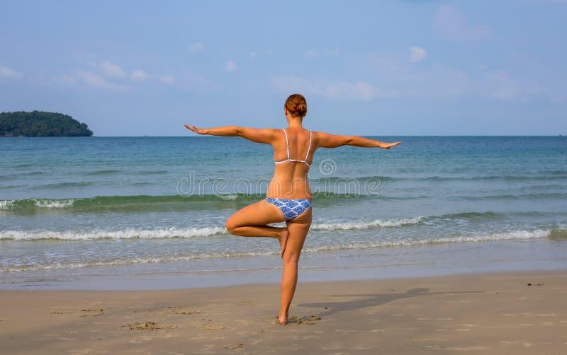 Kvinna som gör yoga på den soliga stranden Tropisk sjösidasemesteraktivitet Ung flicka i asanaställing arkivfoto