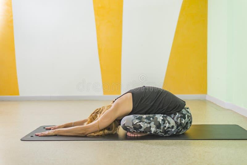 Kvinna som gör yoga på en övning som är matt på yogastudion fotografering för bildbyråer