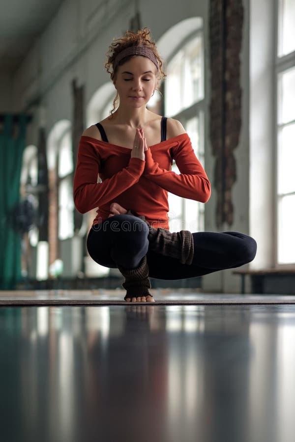 Kvinna som gör yogajämviktsövning på mattt stå på en fot arkivbild