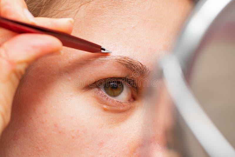 Kvinna som g?r hennes eyebows royaltyfri fotografi