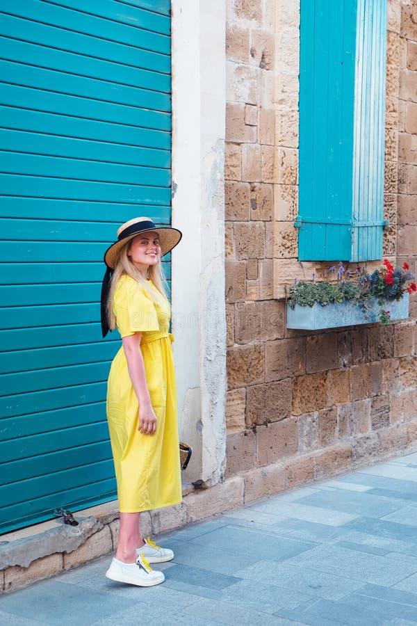 Kvinna som g?r i gul kl?nning p? Paphos den gamla staden royaltyfri foto
