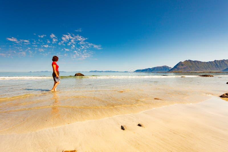 Kvinna som g?r p? den sandiga stranden, Lofoten Norge arkivfoto