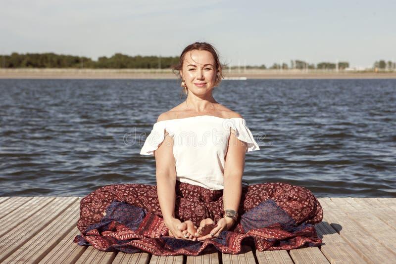 Kvinna som g?r yoga p? sj?n - koppla av i natur arkivfoton
