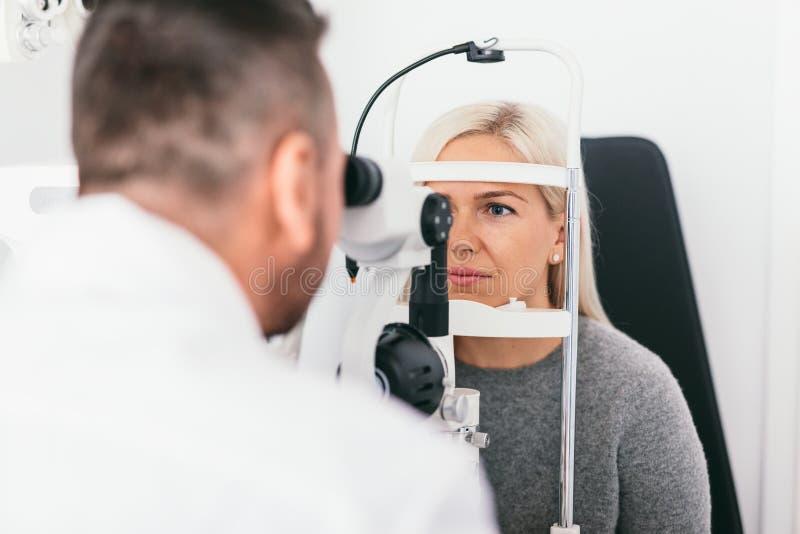 Kvinna som genomgår synförmågaexamen i optiker kontor royaltyfria foton