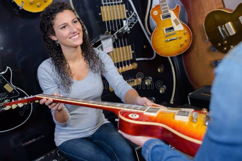 Kvinna som ger en gitarr arkivfoto