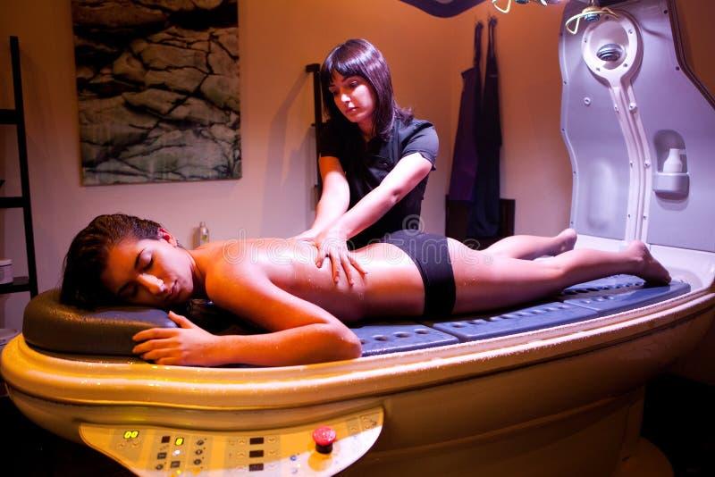 Kvinna som ger en massage under brunnsortbehandling. royaltyfri fotografi