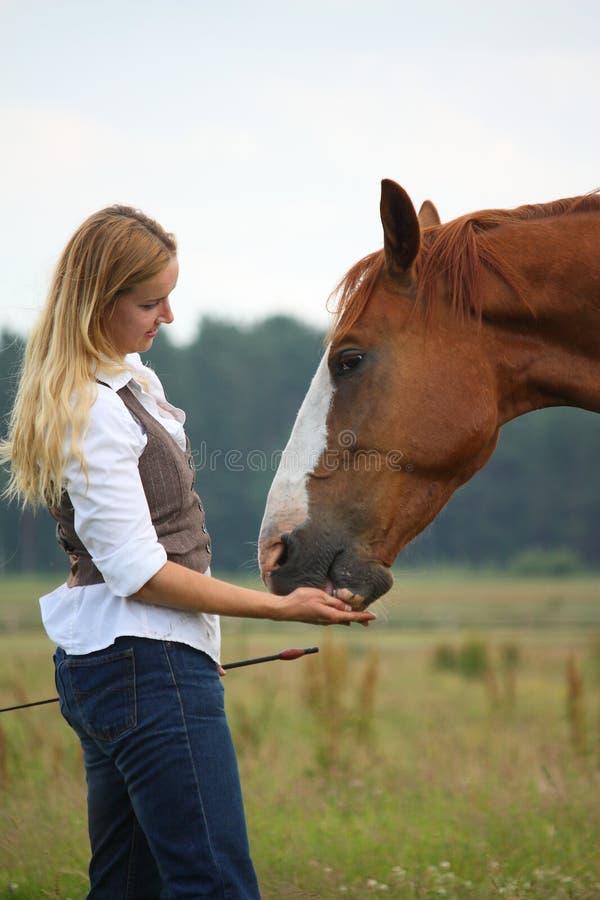Kvinna som ger häst en treat