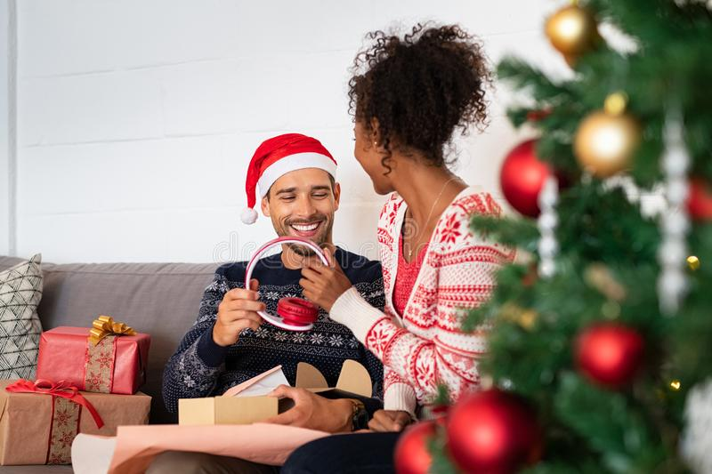 Kvinna som ger julgåvan till hennes pojkvän royaltyfria foton