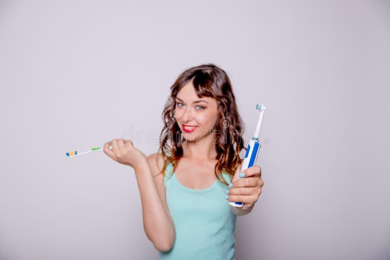 Kvinna som ger mig den elektriska tandborsten Selektivt fokusera Lycklig kvinna som gör ren hennes muntliga hål som att bry sig o royaltyfri foto