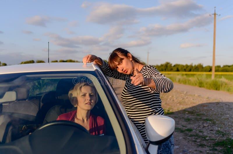 Kvinna som ger riktningar till en kvinnlig chaufför royaltyfri foto
