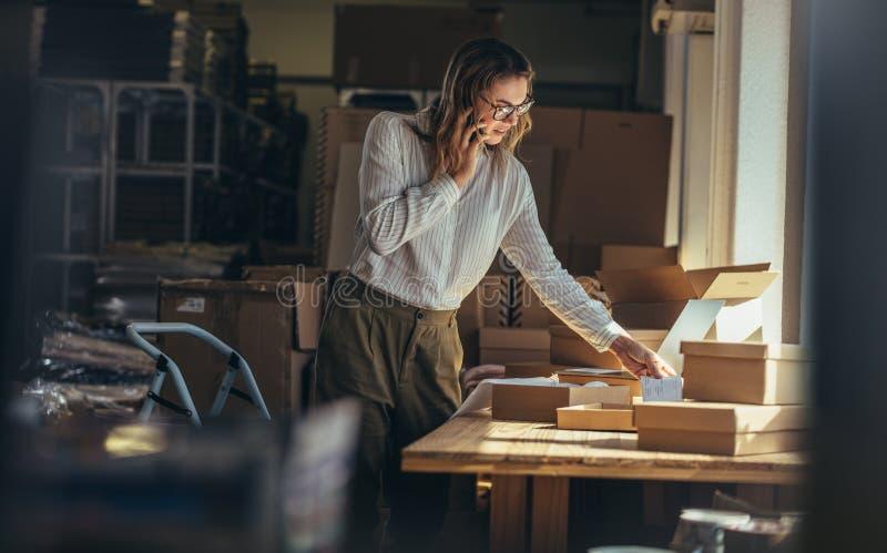 Kvinna som ger sändningsstatusen till kunden fotografering för bildbyråer