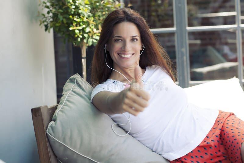 Kvinna som ger tummen upp att le för gest för godkännandehandtecken arkivfoto