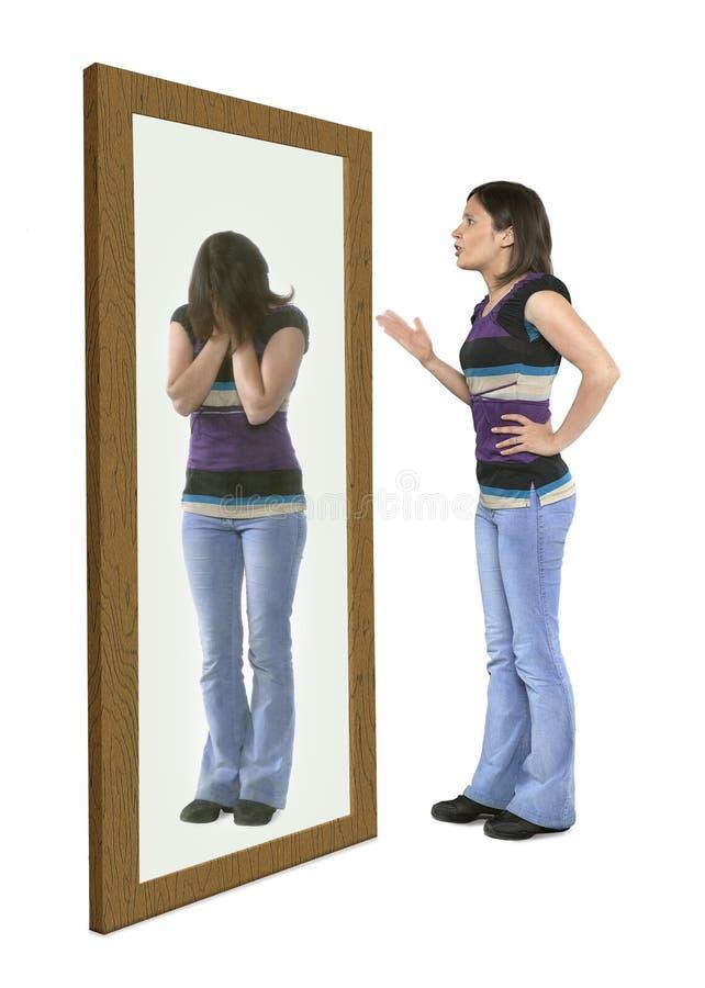 Kvinna som grälar på sig i en spegel royaltyfri foto