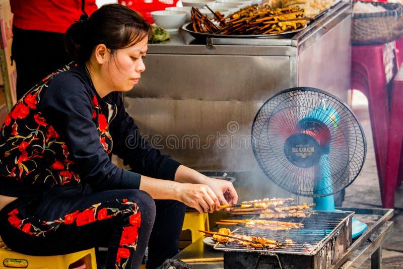 Kvinna som grillar kött Hanoi Asien arkivbild