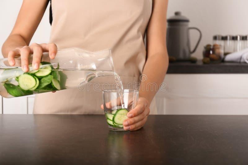 Kvinna som häller smakligt nytt gurkavatten från flaskan in i exponeringsglas på den mörka tabellen royaltyfri fotografi