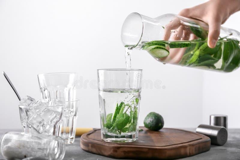 Kvinna som häller smakligt nytt gurkavatten från flaskan in i exponeringsglas på ljus bakgrund arkivfoton