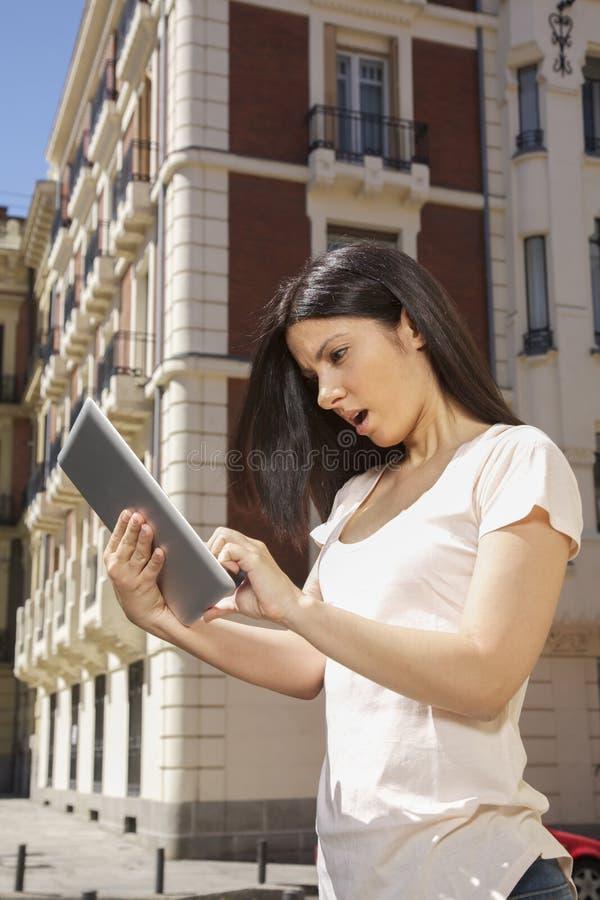 Kvinna som håller ögonen på den digitala minnestavlan royaltyfri bild