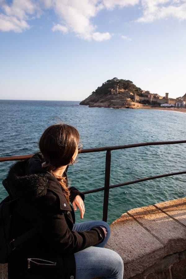 Kvinna som håller ögonen på på den medeltida fästningen på kust nära medelhavs- stad arkivfoto