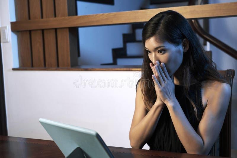 Kvinna som håller ögonen på läskig film arkivbild