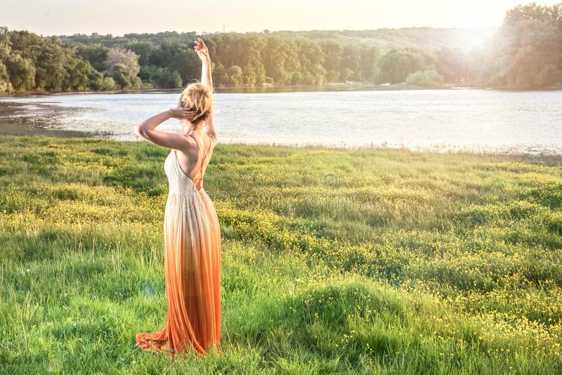 Kvinna som håller ögonen på solnedgången i en lång glamorös klänning älskvärd flicka Härlig landskapsikt, skott från baksidan arkivfoton