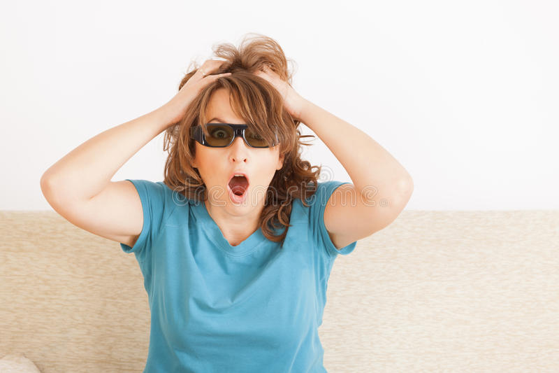 Kvinna som håller ögonen på TV:N 3D i exponeringsglas royaltyfri foto