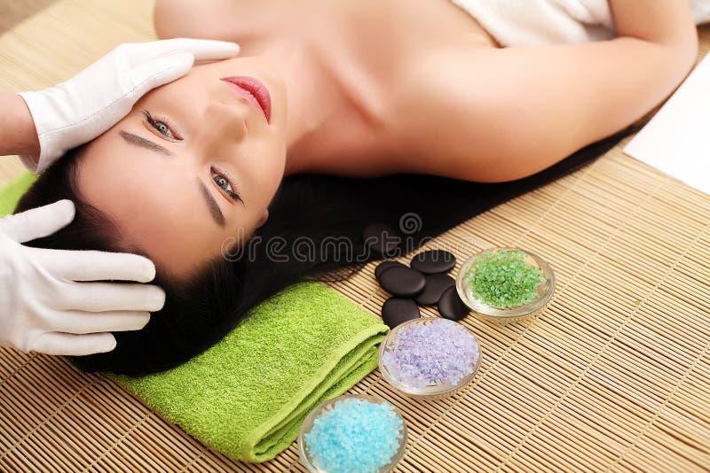 Kvinna som har avslappnande ansikts- massage royaltyfri foto