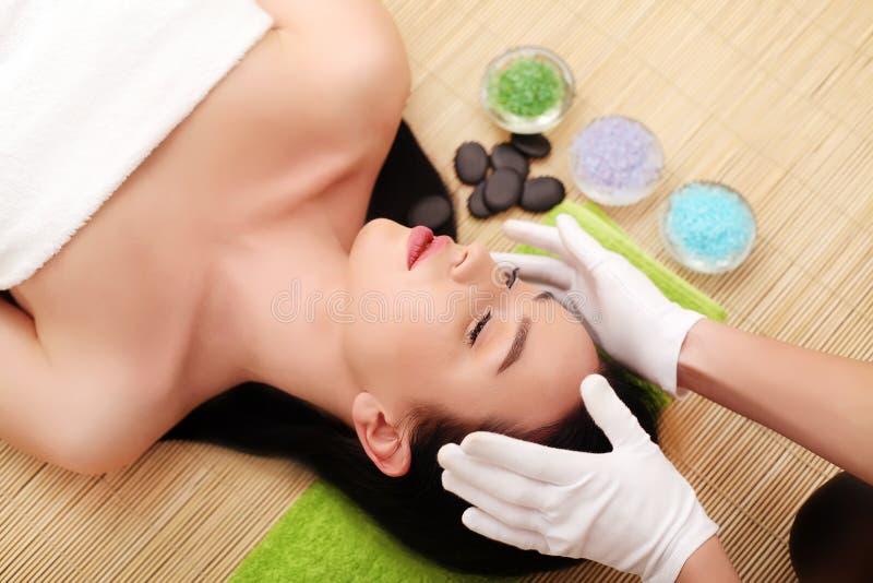Kvinna som har avslappnande ansikts- massage fotografering för bildbyråer