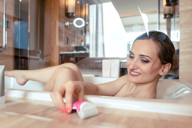 Kvinna som har badet i hotellbadkaret som griper hennes rakapparat arkivfoto