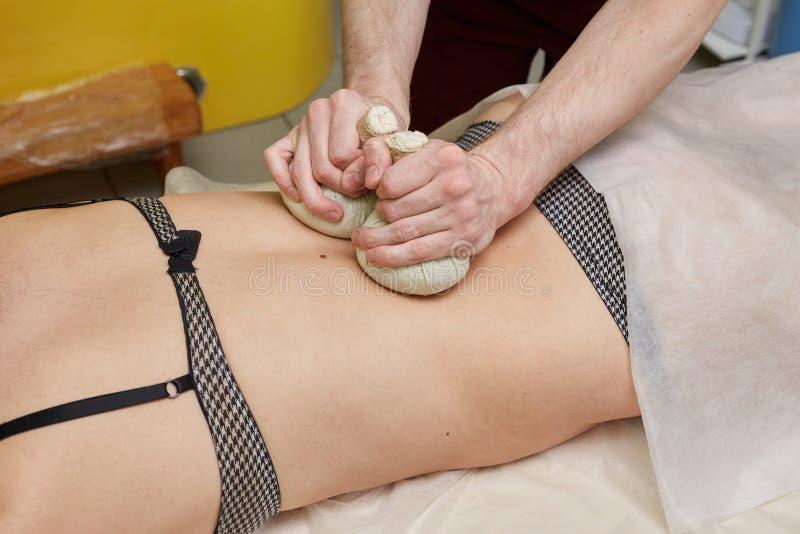Kvinna som har brunnsortpåsemassage i wellnesssalong royaltyfria bilder