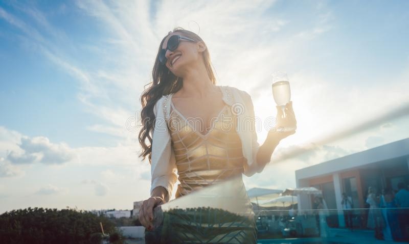Kvinna som har champagne på sommarpartiet arkivbild