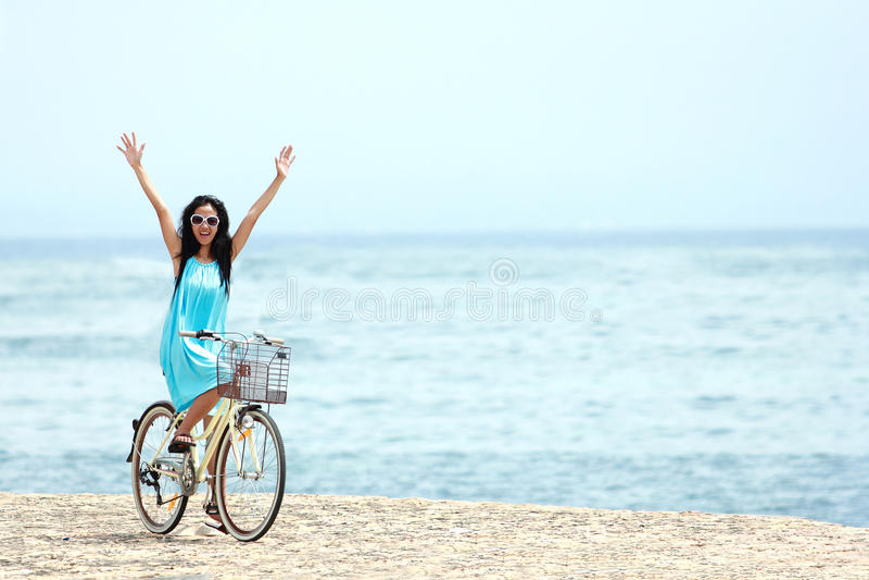 Kvinna som har den roliga ridningcykeln på stranden arkivfoto