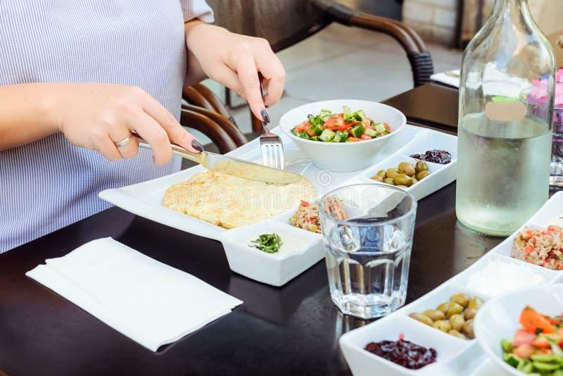Kvinna som har den traditionella israeliska frukosten i morgonen i kafé Portion med äggomelettet, grönsaksallad, lemonad, mellanm arkivfoton