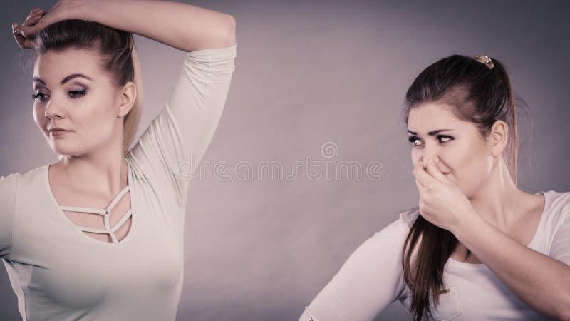 Kvinna som har den våta armhålan hennes vän som luktar stank arkivbild