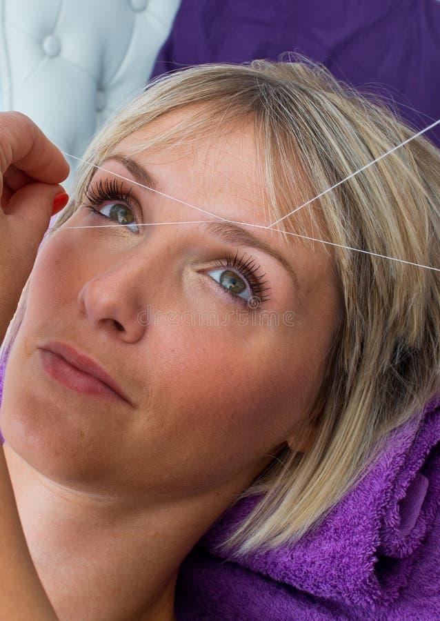 Kvinna som har dragning av hårborttagningstillvägagångssätt royaltyfri foto