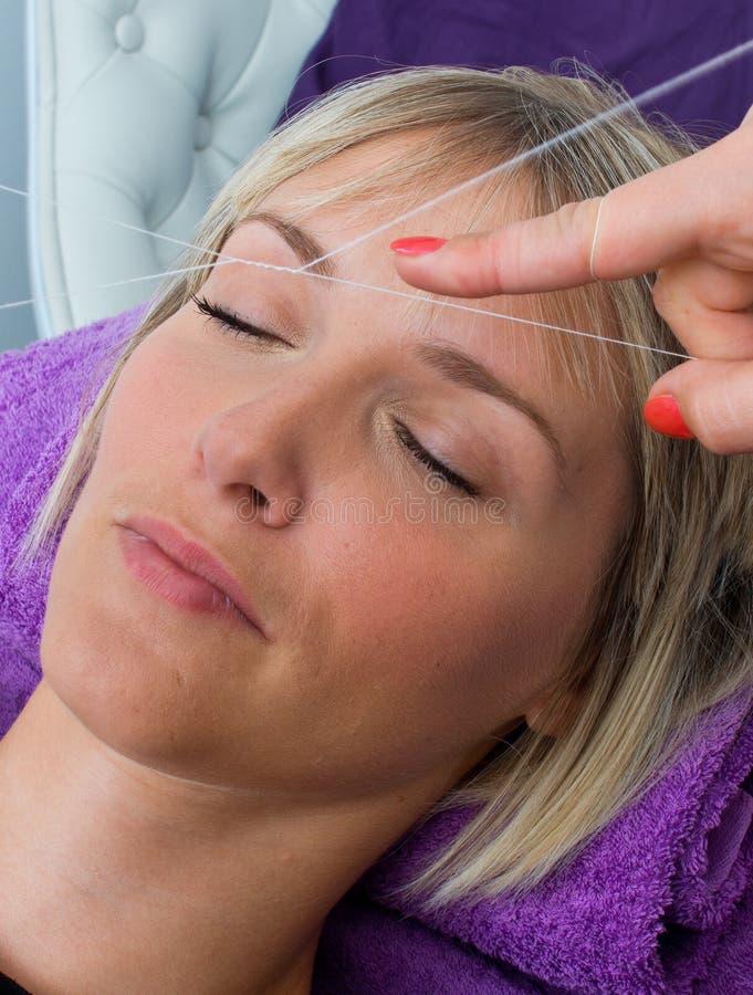 Kvinna som har dragning av hårborttagningstillvägagångssätt arkivbild