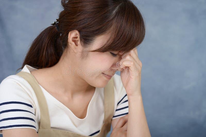 Kvinna som har en huvudv?rk arkivfoton