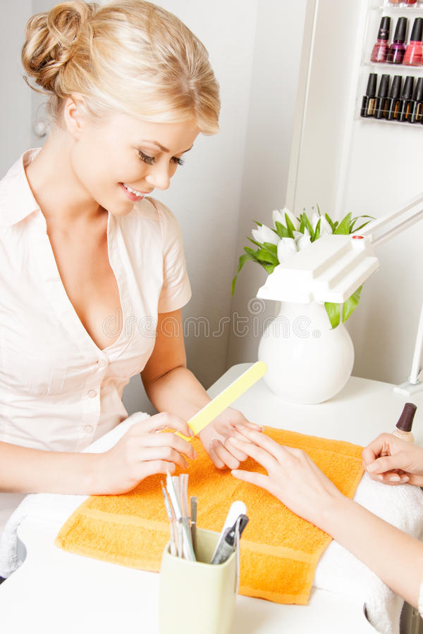 Kvinna som har en manikyr på salongen arkivfoton