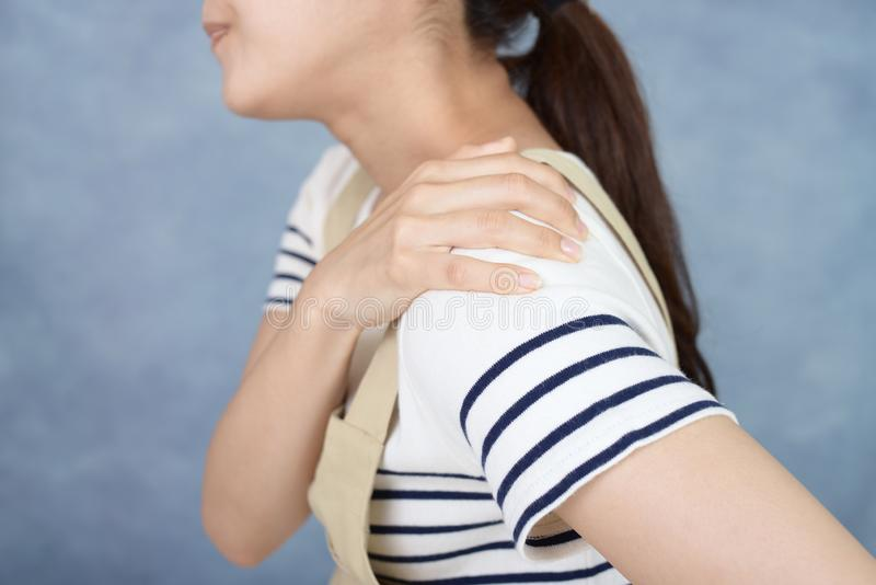 Kvinna som har en skuldra att sm?rta fotografering för bildbyråer